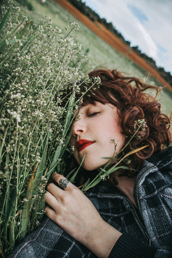 Portrait of beautiful young woman holding plant