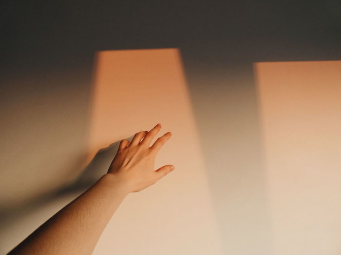 Cropped hand against wall