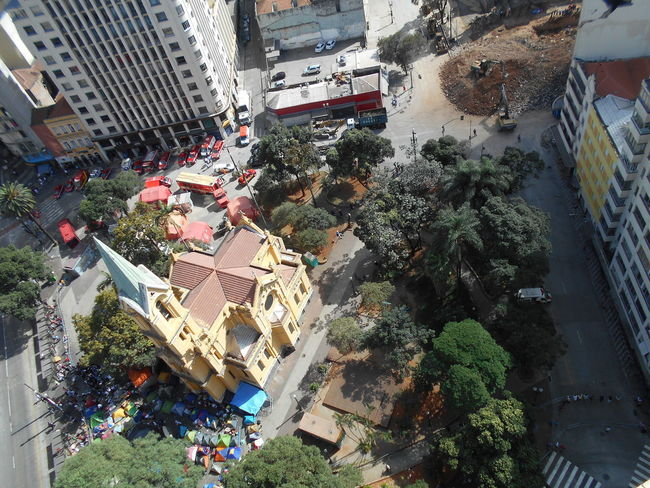Day 9. View of Largo do Paissandú after the building collapse which occurred on May 1st. Building Collapse: Inner City Calamity in downtown São Paulo at Largo do Paissandú; 3 am May 1, 2018. The abandoned former Federal Police steel and glass skyscraper, which had been invaded by street people, imploded in the early morning hours and the neighboring buildings, including the Lutheran Church on Avenida Rio Branco, were destroyed by fire as well. This high angle view from my 23rd floor perspective captures the current state of affairs -- the growing displaced homeless outdoor camp in front of the church Nossa Senhora do Rosário dos Homens Pretos; the firefighters and police permanently stationed behind the church; and, the work-in-progress for the debris removal of the collapsed building. Current Events Focus On The Story Igreja Nossa Senhora Do Rosário Dos Homens Pretos Largo Do Paissandu May 1, 2018 May 9, 2018 Susan A. Case Sabir Unretouched Photography Bright And Sunny Building Collapse Controlled Chaos Day 9 Displaced Homeless Downtown São Paulo High Angle View Implosion Not A Drone Photo Responsiveness Social Issue Of Public Housing With Dignity Urban Photography Urban Strife Work-in-progress