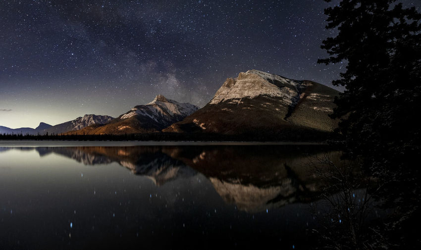 Reflection of trees in lake against sky at night