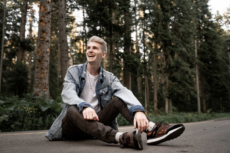 Cheerful young man sitting on road in forest