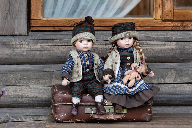 Ancient porcelain dolls sits on suitcase near log farmhouse. Ancient Antique Baby Bear Dresses Farm Farmhouse Fashion Hat Porcelain  Sitting Toys Wood Boy Ceramic Clothes Dolls Girl Log Old Porcelain Doll Style Suitcase Vintage Wooden