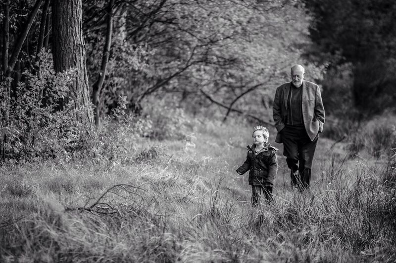 Man And Boy Walking In Forest