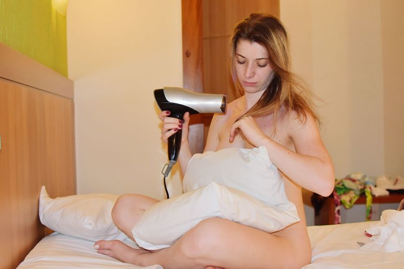 Full length of naked woman drying hair while sitting on bed at home