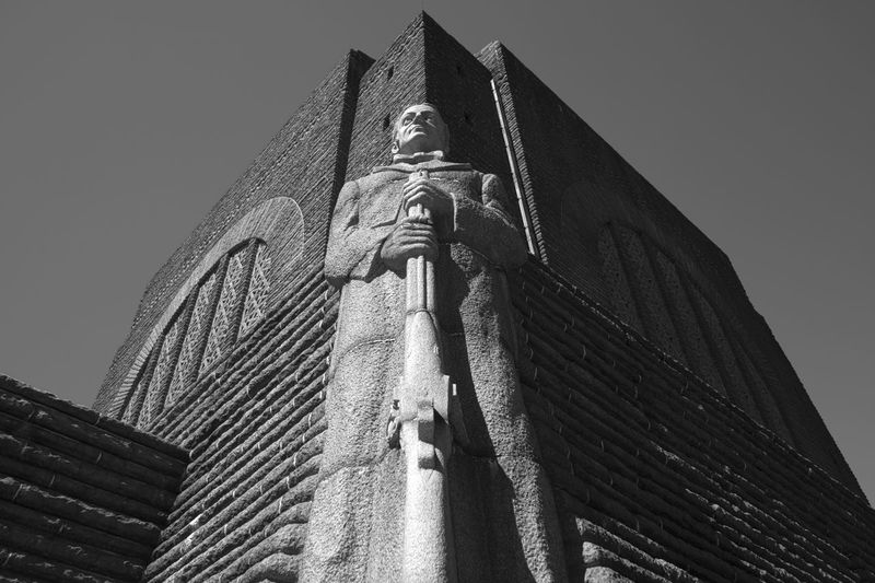 Low angle view of a statue at the base of the Voortrekker monument. Architecture Art And Craft Belief Building Building Exterior Built Structure Clear Sky Creativity Day Human Representation Low Angle View Male Likeness Nature No People Religion Representation Sculpture Sky Spirituality Statue