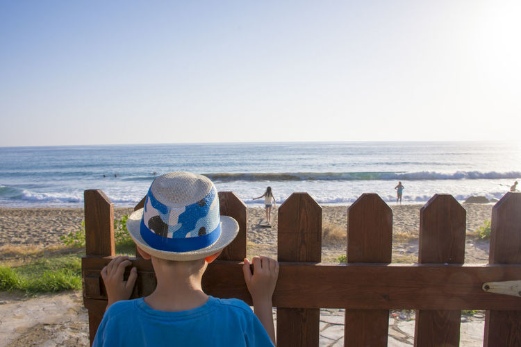 Rear view of boy standing by fence against beach