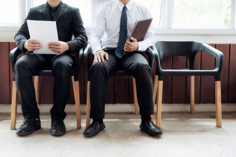 Low section of businessmen sitting on chairs