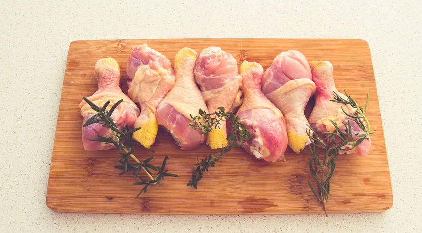 Chicken drumsticks on a cutting board with fresh rosemary and thyme. Chicken Drum Stricks Chopping Board Cutting Board Day Food Food And Drink Freshness High Angle View Indoors  Lamb - Meat Meat No People Raw Chicken Raw Food Raw Food Photography Rosemary Herb Rustic Table Thyme Plant Wood - Material Wooden Board