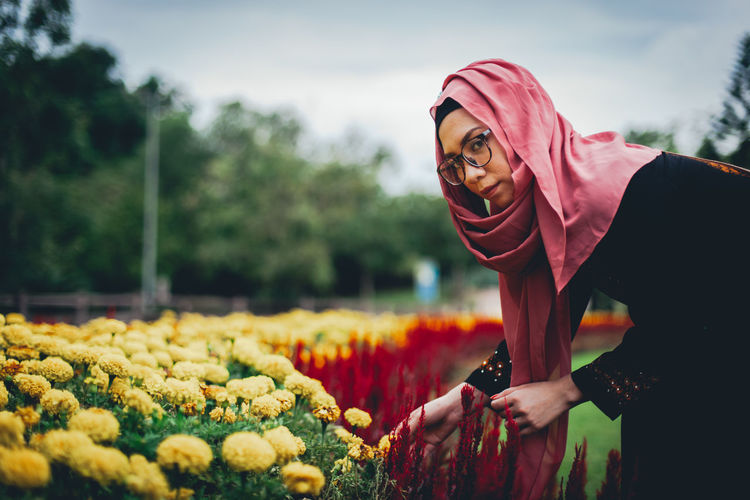 Portrait of young woman by flowers at park