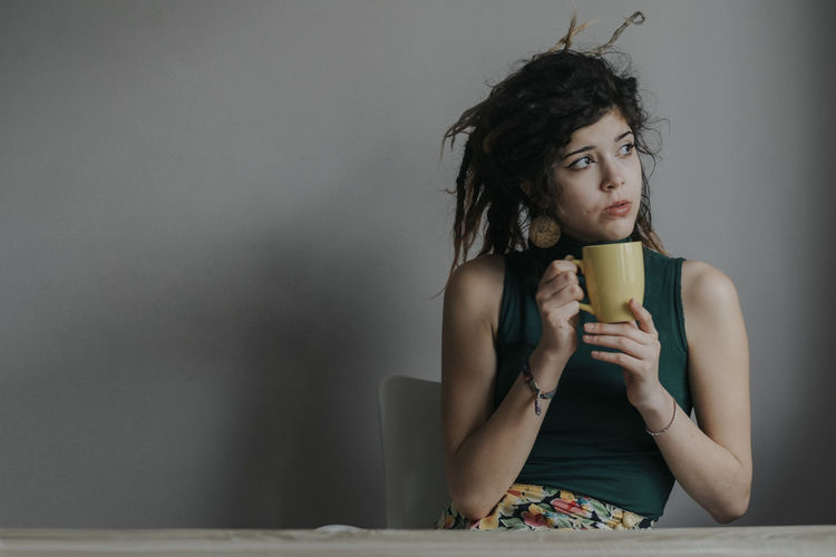 Portrait of a young female model with dreadlocks drinking coffee at home Holding Hands Liquid Textured  Careless Contemplation Cup Dreadlocks Drink Drinking Food And Drink Front View Hairstyle Hippie Hippielife Holding Indoors  Lifestyles Looking Looking Away One Person Portrait Real People Sitting Teenager Young Adult