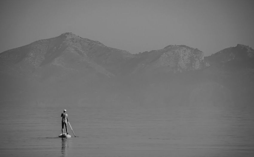 Rear View Of Person Paddleboarding In Sea During Foggy Weather