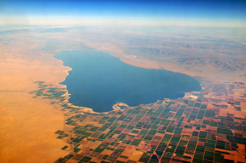 Aerial view of salton sea amidst field against sky