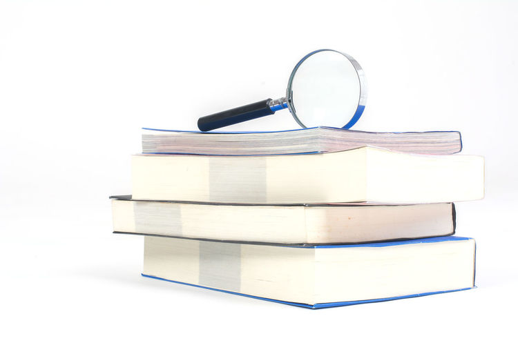 Close-up of magnifying glass on stacked books against white background