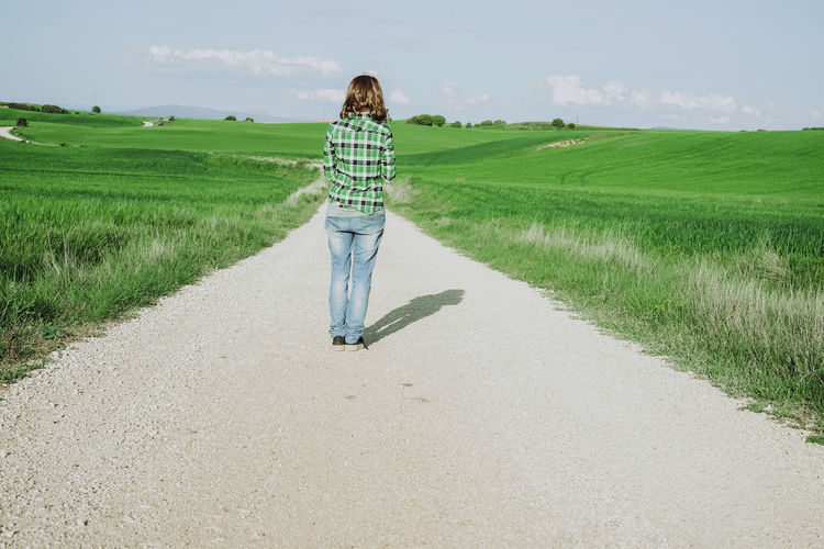 One Person Casual Clothing Real People Direction Land Full Length Grass Plant Road The Way Forward Field Landscape Lifestyles Day Rear View Sky Nature Leisure Activity Green Color Environment Outdoors Diminishing Perspective Freshness Fresh Green Green Color Springtime Spring Nature Standing Waiting Alone Alone Time Loneliness Path Rural Scene Countryside Summer Plaid Jeans Horizon Woman Backgrounds Back View
