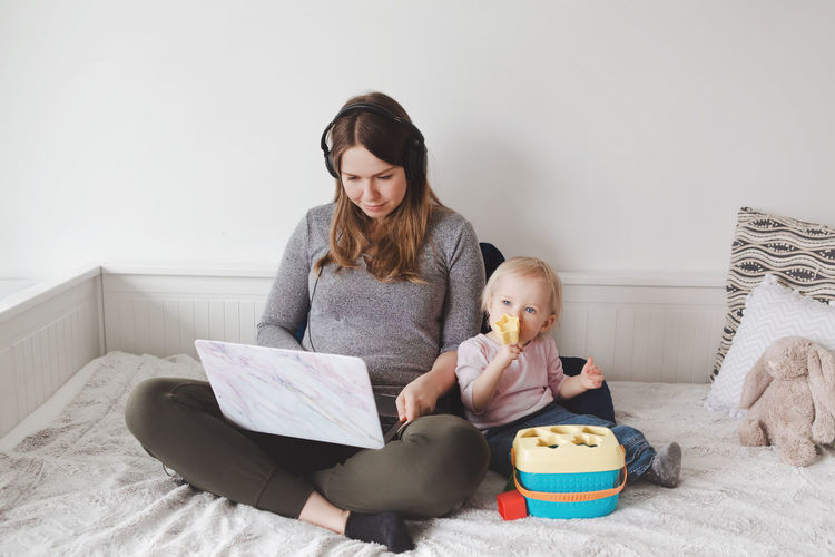 High angle view of woman working on laptop sitting with baby on bed at home
