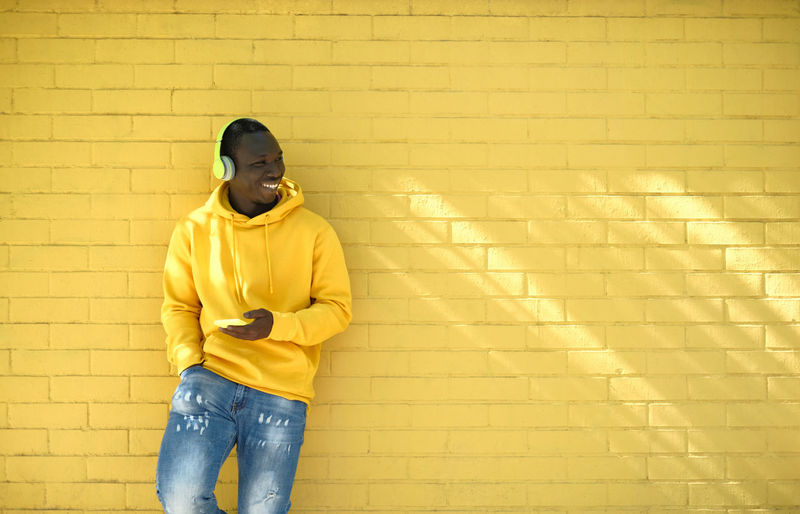 Full length of a man standing against yellow wall