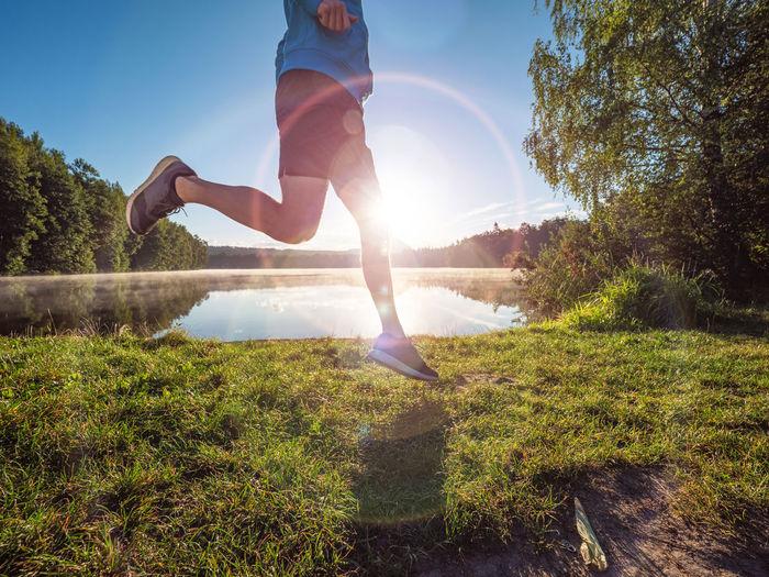 Man jumping on field against bright sun