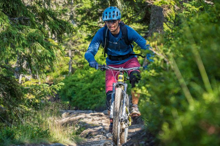 Man riding a mountain bike on footpath in the austrian alps, saalbach, austria
