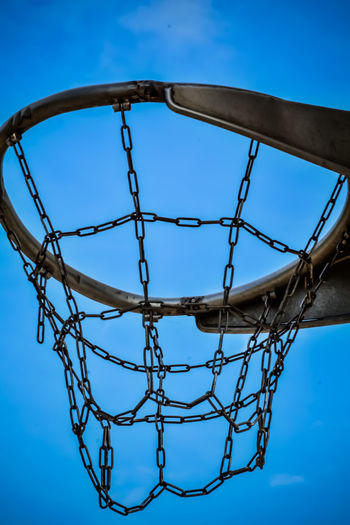 Low Angle View Of Metallic Basketball Hoop Against Blue Sky