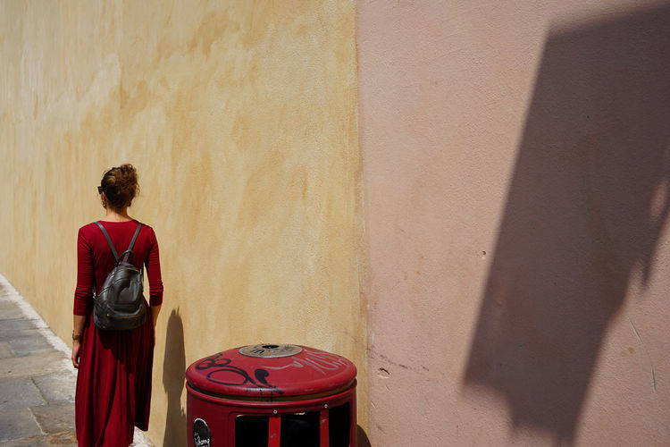 Rear view of woman in red dress walking by wall