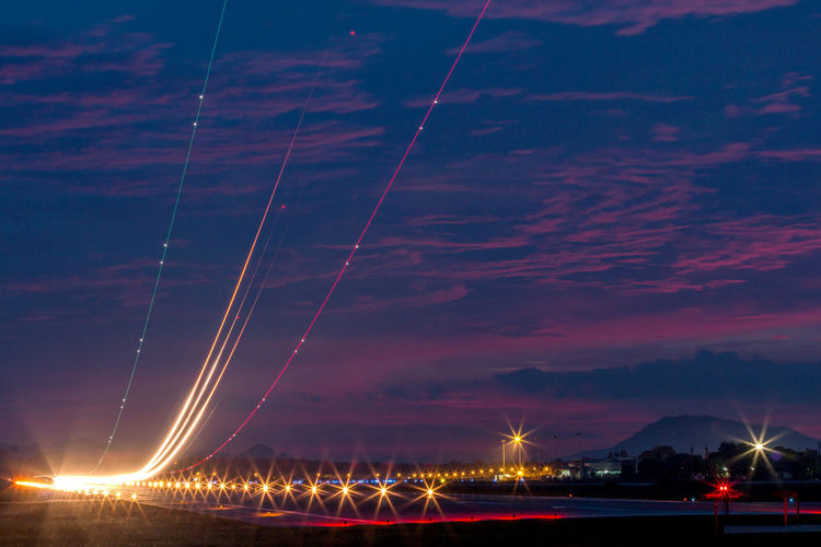 Light trails at airport runway against cloudy blue sky at dusk