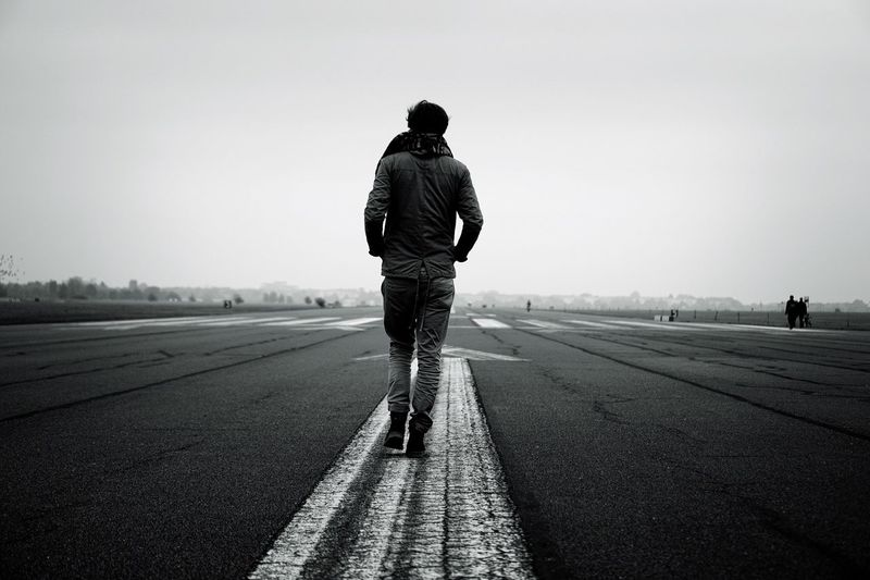 Rear View Of Solitary Man Walking Forward