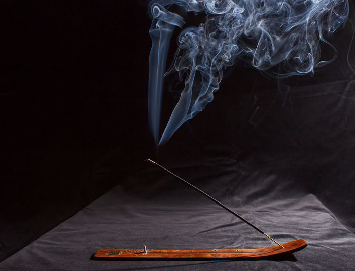 Close-up of smoke emitting from cigarette on table