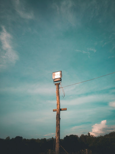 Low angle view of telephone pole against sky at dusk