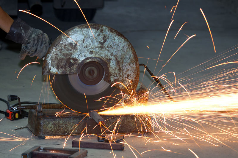 Cropped hand of worker cutting metal