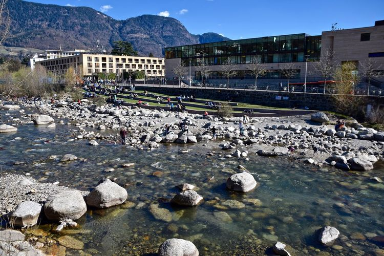 River against buildings and mountains on sunny day