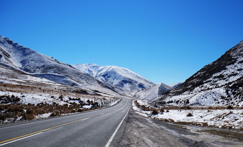 Road amidst snowcapped mountains against clear blue sky