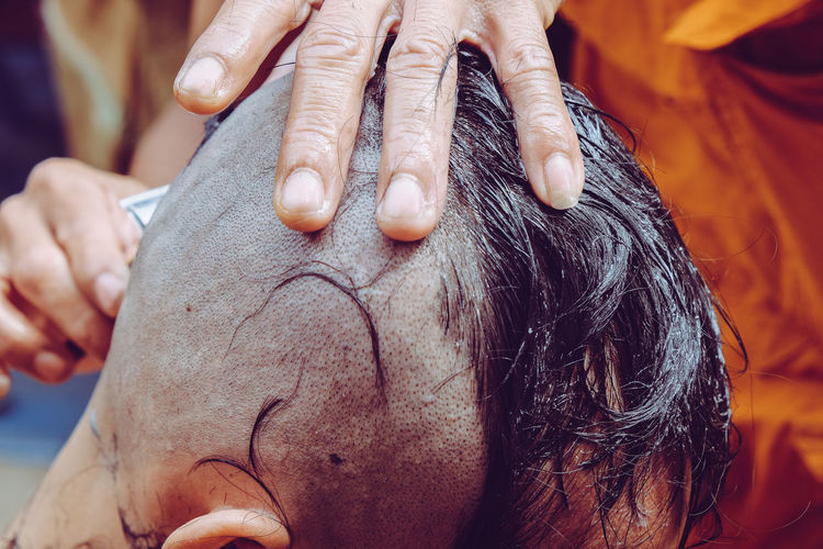 Cropped hands of barber shaving customer head