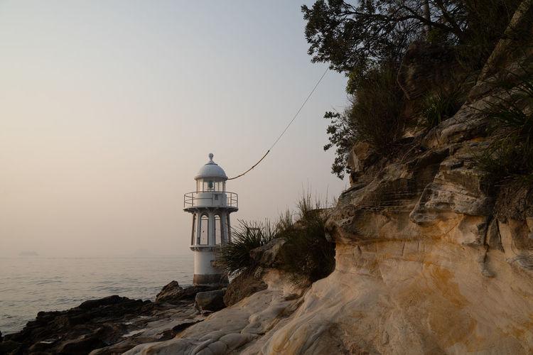 Lighthouse by sea against sky