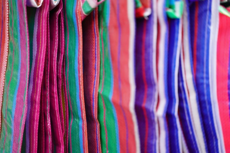 Full frame shot of multi colored shopping bags hanging at market stall