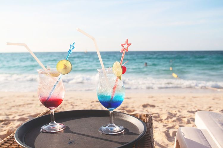 Close-up of wine glasses on beach against sky