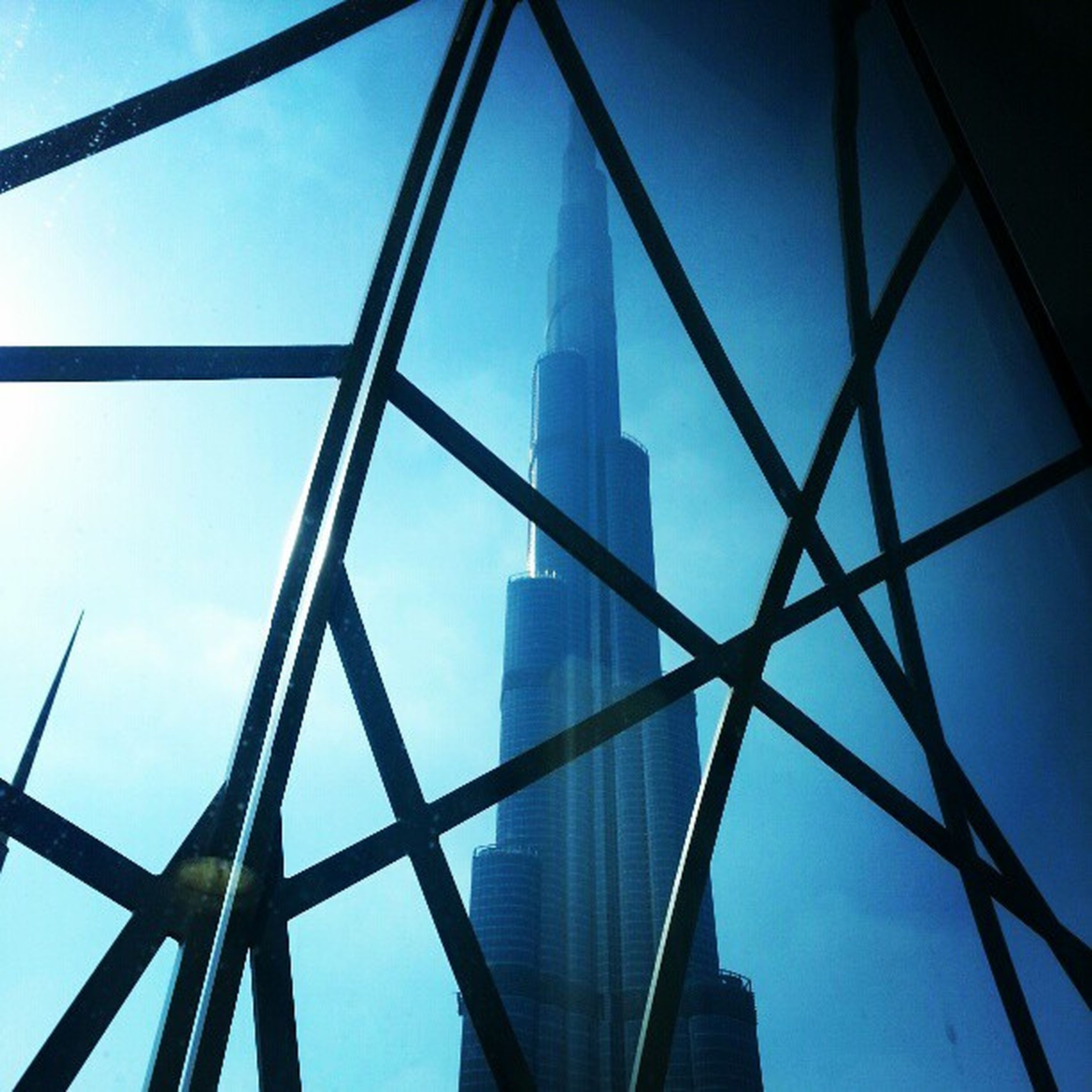 low angle view, built structure, architecture, clear sky, blue, sky, tall - high, building exterior, metal, tower, modern, day, grid, glass - material, metallic, no people, outdoors, skyscraper, city, office building