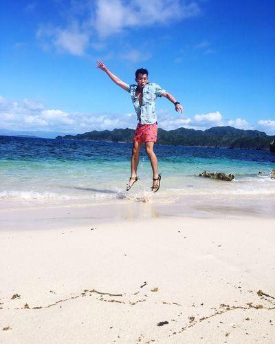 Full Length Of Man Jumping On Shore At Beach Against Sky