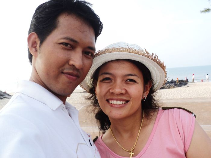Portrait of smiling couple at beach against sky