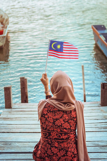 Rear view of woman wearing hijab holding malaysian flag sitting on pier by lake