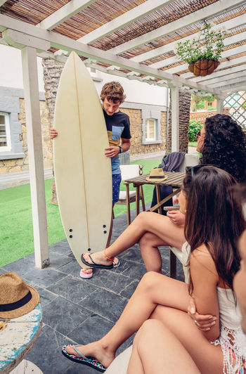 Young female friends looking at man holding surfboard