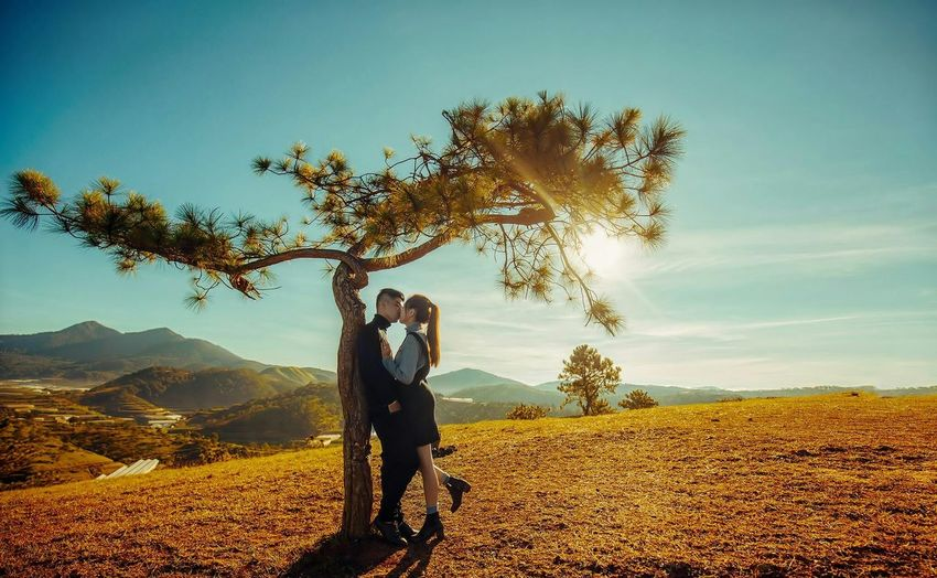 Side view of young couple kissing while standing on mountain against sky during sunny day