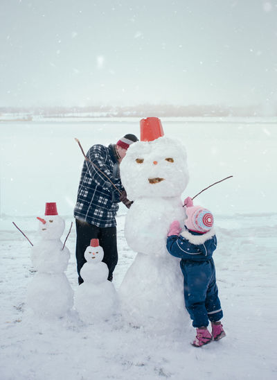 Man and his little daughter making a snowman, spending time together outdoors, having fun on snow in wintertime. Dad and kid wearing warm clothes Winter Wintertime Snowman Fun Snow Snowing Outdoors Lifestyles Cold Wintery Season  White Enjoyment Leisure Happiness Child Childhood Girl Kid Family People Siblings Man Dad Father