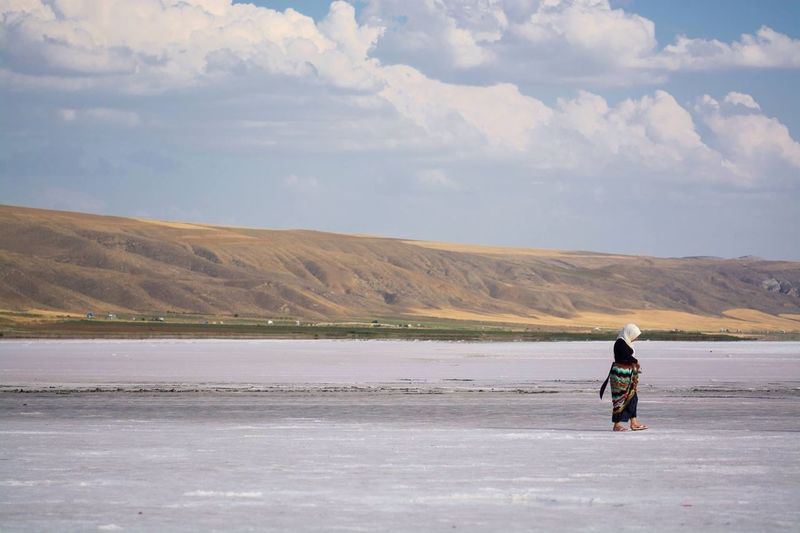 Full length of woman in hijab walking on frozen river against cloudy sky