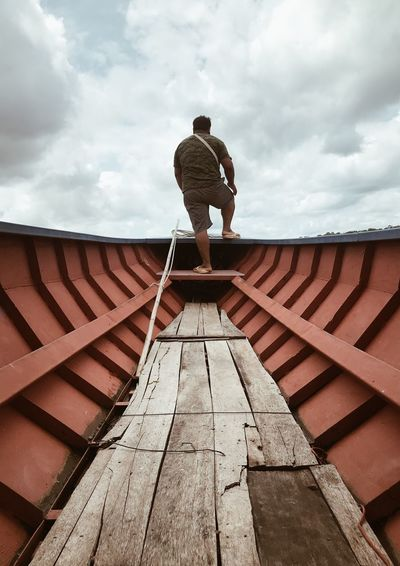 Rear view of man standing in boat against sky