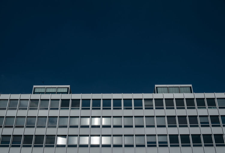 Low angle view of modern office building against clear blue sky