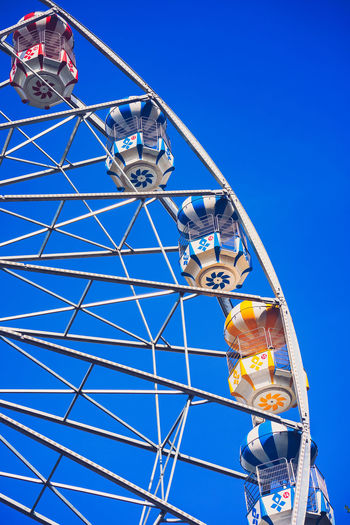 Ferris wheel with blue background Sky Low Angle View Amusement Park Blue Amusement Park Ride Ferris Wheel Clear Sky Leisure Activity Day Nature Arts Culture And Entertainment Men Sunlight Real People Built Structure Metal People Outdoors Architecture Fun Ferris Wheel Fun Blue Background