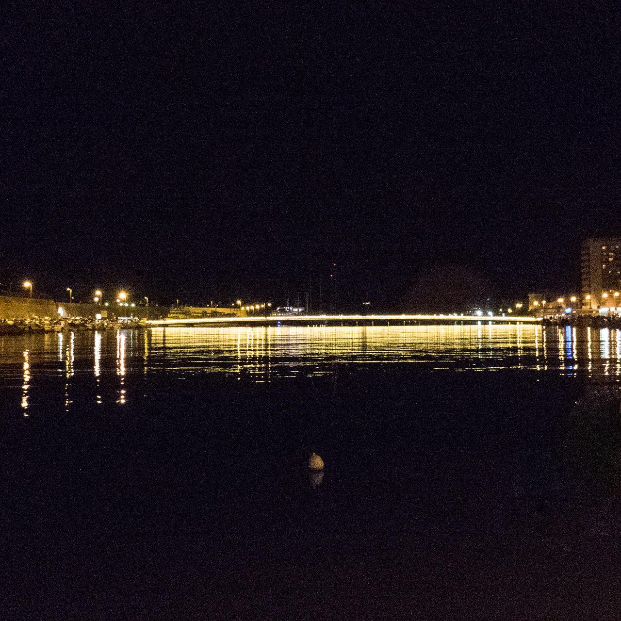 REFLECTION OF ILLUMINATED CALM SEA IN THE DARK
