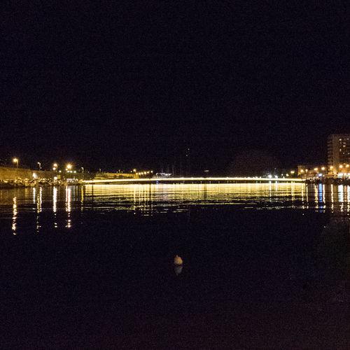 Reflection of illuminated sky on calm sea at night