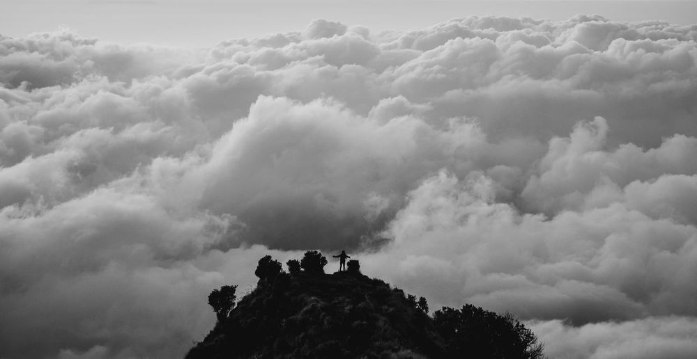 Person on mountain against cloudy sky