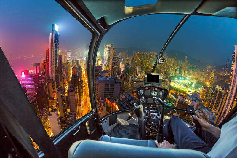 Midsection of pilot flying helicopter over illuminated city at night